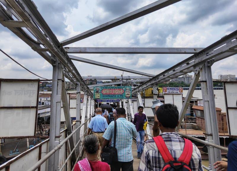 KOLKATA, INDIA - JULI 24, 2019: De mensen lopen op een werf om de openbaar vervoerboot bij rivier Hoogly te halen Binnenvaart stock foto's