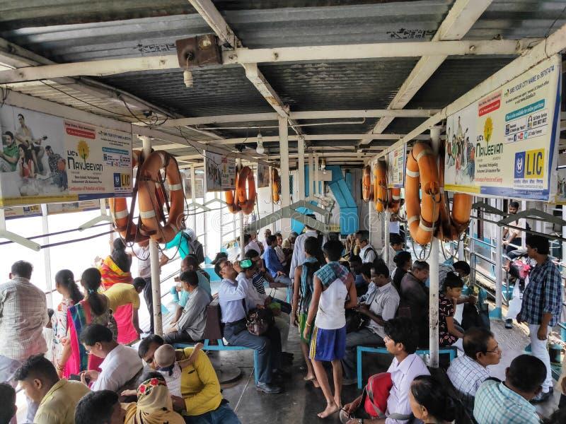 KOLKATA, INDIA - JULI 24, 2019: Mensen op de openbaar vervoerboot bij rivier Hoogly worden gezeten die Binnenvaart stock foto