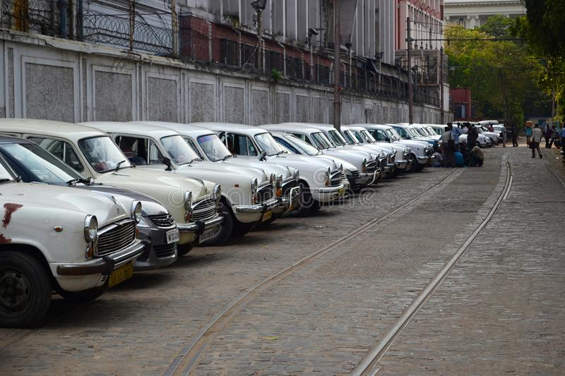 Classic ambassador cars in a row. Kolkata, India - March, 2014: Row of old vintage Ambassador white cabs along tram tracks in Calcutta. Classic cars in row stock images