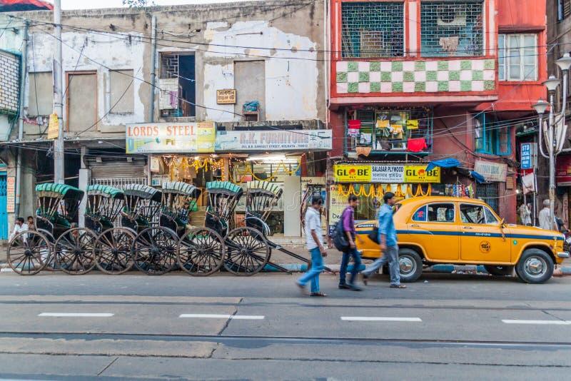 KOLKATA, INDIA - OKTOBER 30, 2016: Getrokken riksja en gele Hindustan-Ambassadeurstaxi in het centrum van Kolkata, Ind. stock foto