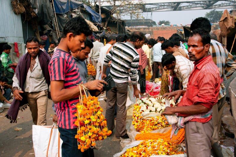 KOLKATA, INDIEN: ?ustomers sind die Händler des gedrängten Blumenmarktes verbunden lizenzfreie stockfotografie