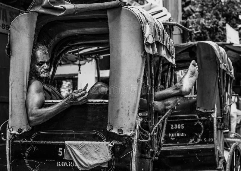 Kolkata, Indien - den 28 augusti 2019: Rickshaw puller vilar på sin rickshaw på kolkata gata arkivfoton