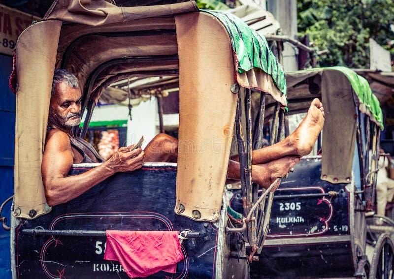 Kolkata, Indien - den 28 augusti 2019: Rickshaw puller vilar på sin rickshaw på kolkata gata arkivbilder