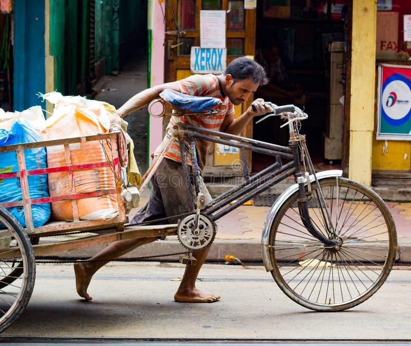 Kolkata, Indien - den 28 augusti 2019: Rickshaw van puller på gatan Kolkata, som drar hårt för att dra tung last royaltyfri fotografi
