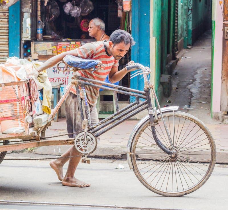 Kolkata, Indien - den 28 augusti 2019: Rickshaw van puller på gatan Kolkata, som drar hårt för att dra tung last arkivbild