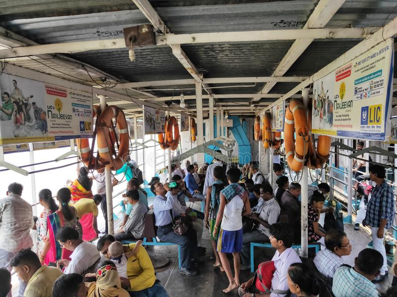 KOLKATA INDIEN - JULI 24, 2019: Folket satt på kollektivtrafikfartyget på floden Hoogly Flodtransport arkivfoto