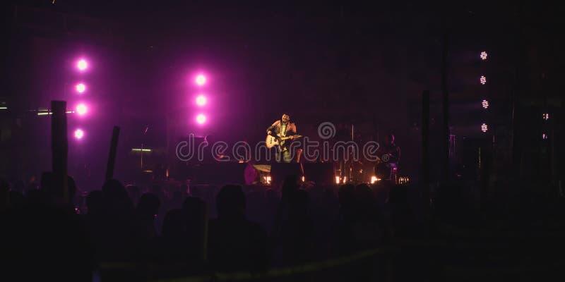 Kolkata Indien 1 Maj 2019: Gitarrist som utför på Vagga konsertmötesplatsen med den tända ljusa färgrika etappljus och konturn av arkivbilder