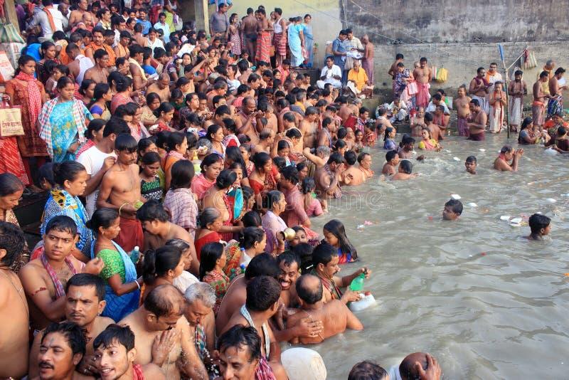Kolkata Indien - Oktober 12: Det hinduiska folket tar ett bad i rien royaltyfri foto