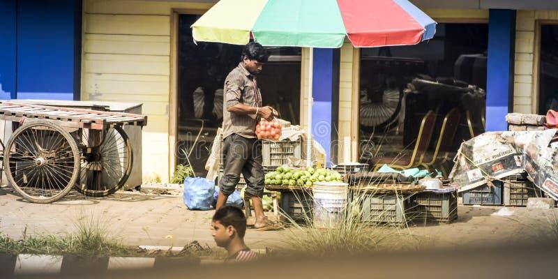 Kolkata la India mayo de 2018 - hombre con el bolso que hace compras plástico que camina abajo de la calle de la ciudad a pesar d imagenes de archivo