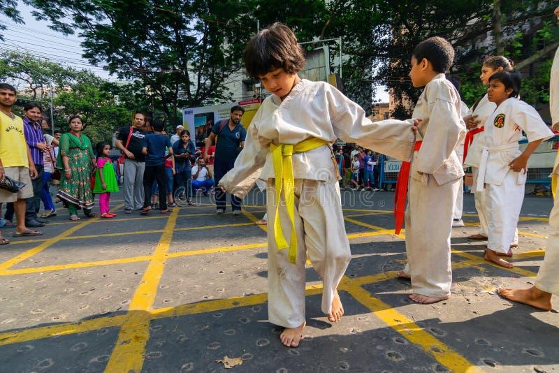 KOLKATA VÄSTRA BENGAL, INDIEN - MARS 21ST 2015: Härlig ung flicka i den vita klänningen för karateutbildning arkivbild