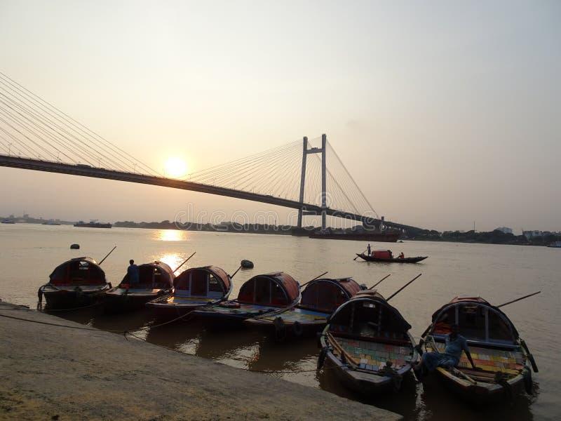 Kolkata Vidyasagar Setu bro med fartyg under solnedgång royaltyfria foton