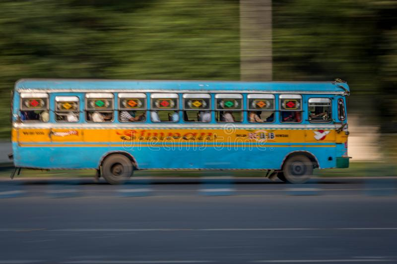 A fast moving public bus with passengers on streets of Kolkata, Calcutta, West royalty free stock photography