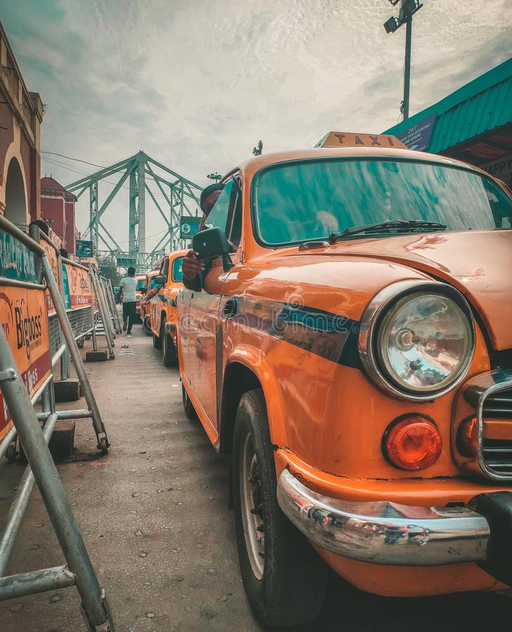Kolkata, West Bengal: Outside Howrah Railway Station. Taxi line up for picking passengers. Howrah Bridge in background stock images