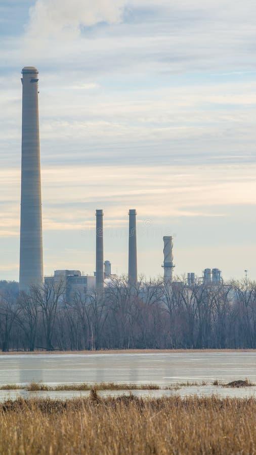 Kolkraftväxt med gaser och föroreningar som kommer ut ur rökbuntar - av den Minnesota floden och den viktiga fågelflyttningsrutte arkivbild
