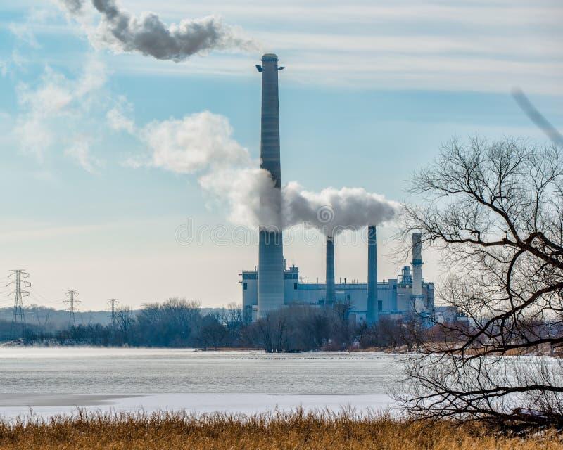 Kolkraftväxt med gaser och föroreningar som kommer ut ur rökbuntar - av den Minnesota floden och den viktiga fågelflyttningsrutte royaltyfri foto