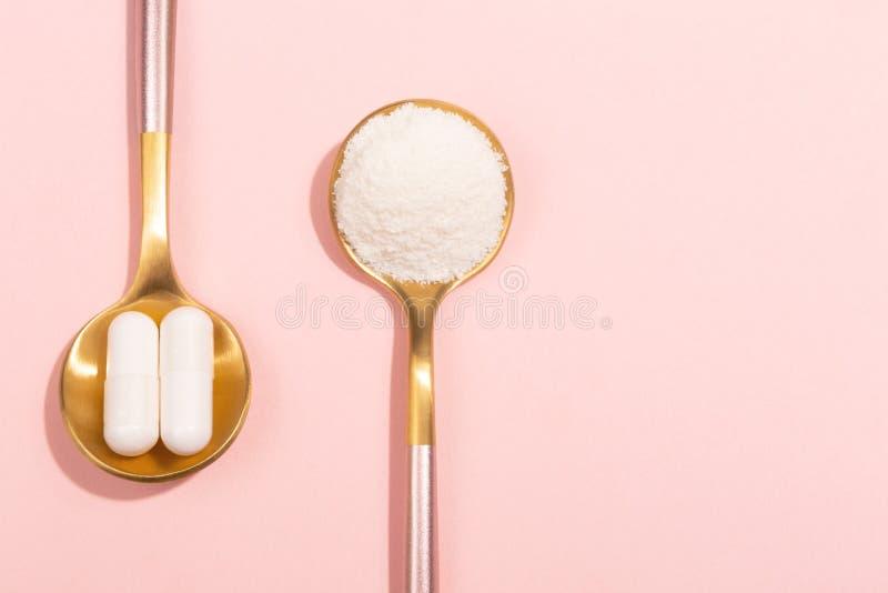 Kollagenpulver und -pillen auf rosa Hintergrund stockfotografie