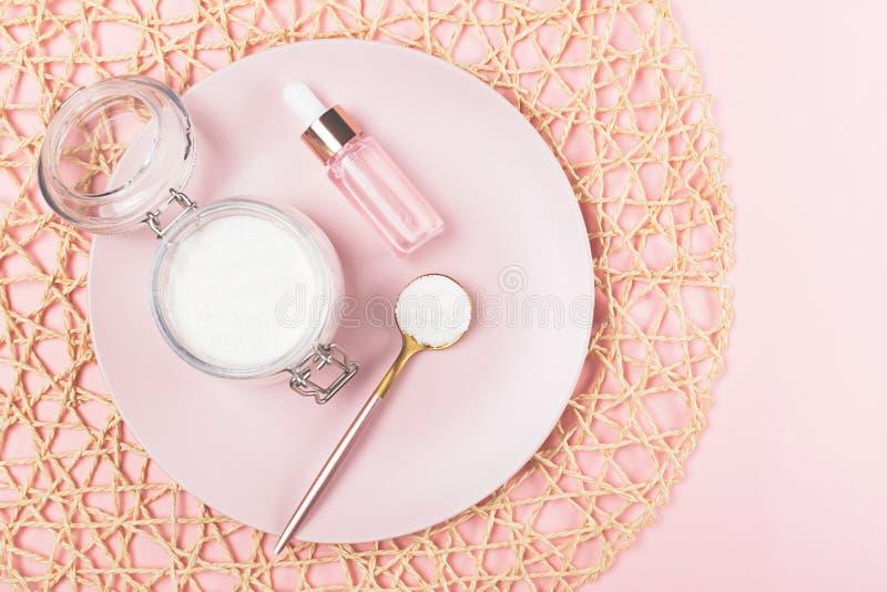 Kollagenpulver und Serumflasche auf rosa Hintergrund stockfotos