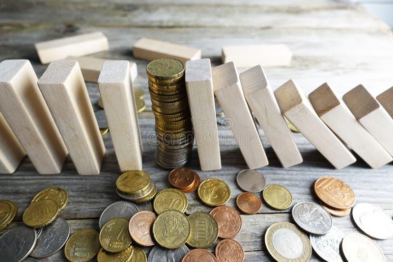 Kollaps av valutakursbegreppet, med högen av mynt mellan trästycken som dominobricka arkivfoto