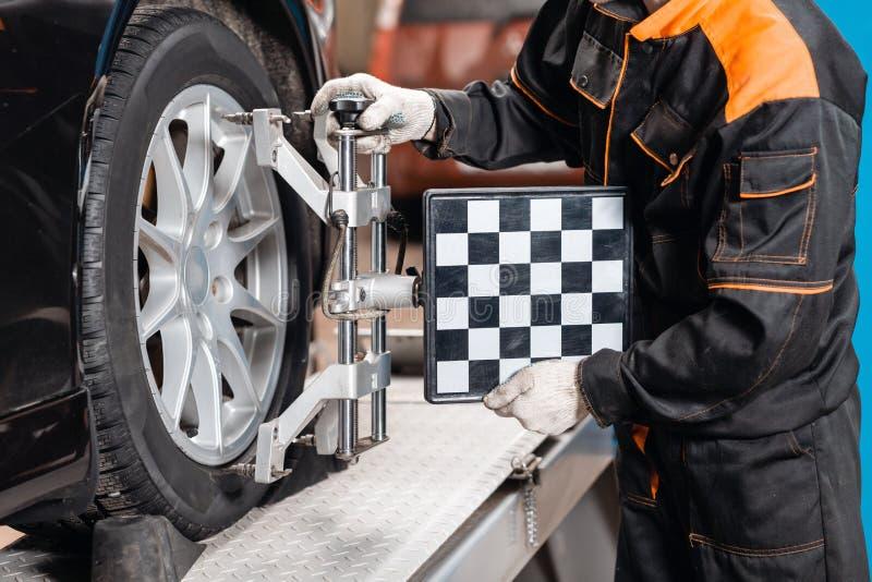 Kollaps-konvergens Den auto mekanikern st?ller in bilen f?r diagnostik och konfiguration Utrustning f?r bilhjuljustering p? royaltyfri foto