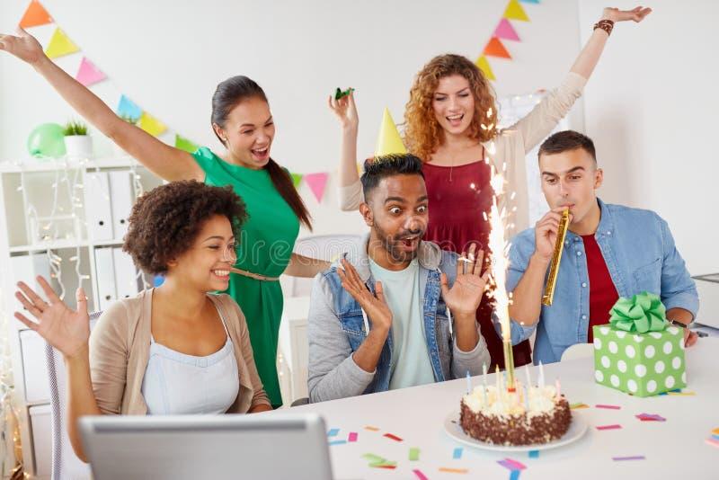 Kollega för kontorslaghälsning på födelsedagpartiet arkivfoto