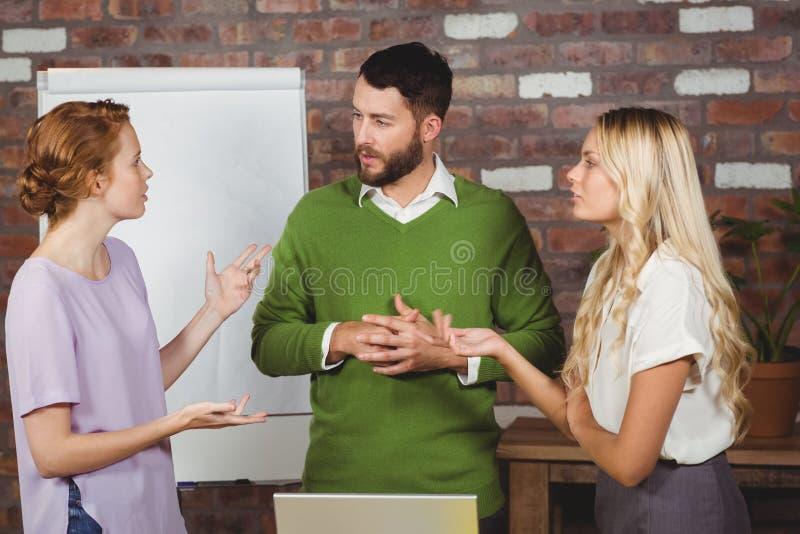 Kollegen, die über Arbeit im Büro sprechen lizenzfreie stockfotografie