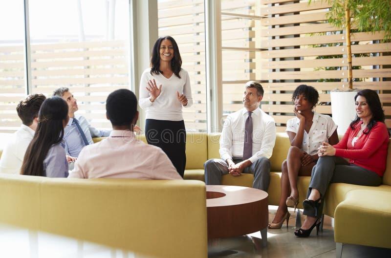 Kollegen, die auf Darstellung durch einen weiblichen Manager hören stockfotos
