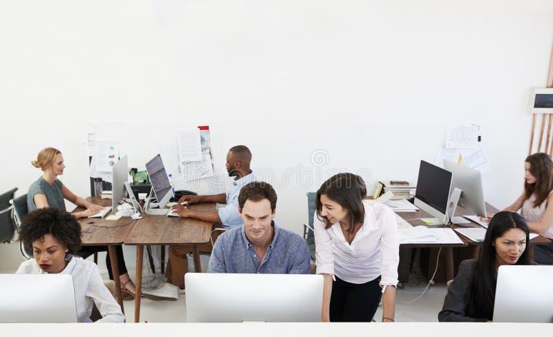 Kollegen, die bei der Arbeit in einem beschäftigten Bürogroßraum sprechen lizenzfreies stockfoto