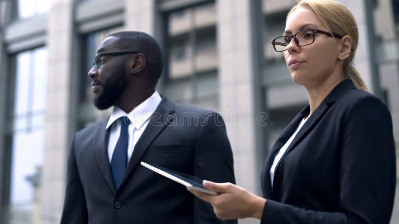 Kollegen, die bei der Arbeit, rassisch oder sexueller Diskriminierung, Respektlosigkeit streiten stockbild