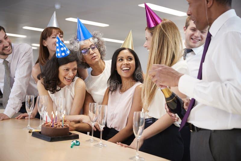 Kollegen, die einen Geburtstag im offenen Champagner des Büros feiern stockfotografie