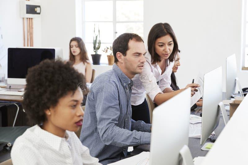 Kollegen, die oben bei der Arbeit in einem beschäftigten Bürogroßraum, Abschluss sprechen lizenzfreie stockfotos
