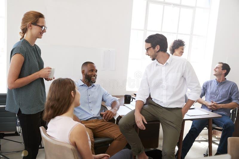 Kollegen, die oben eine zufällige Sitzung in ihrem Büro, Abschluss genießen lizenzfreies stockfoto