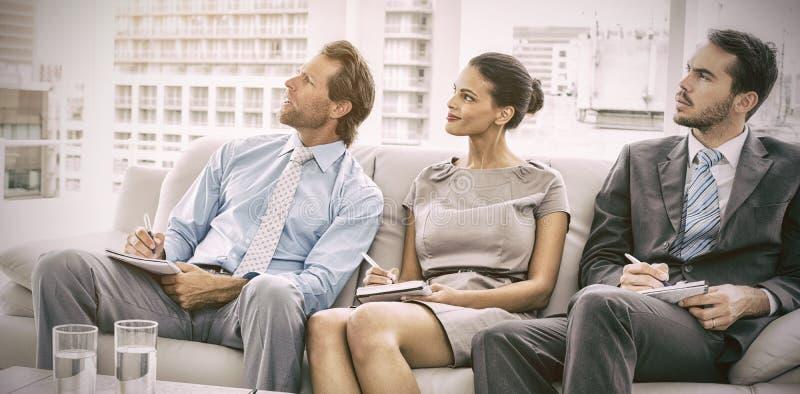 Kollegor med anmärkningar i möte på kontoret royaltyfri foto