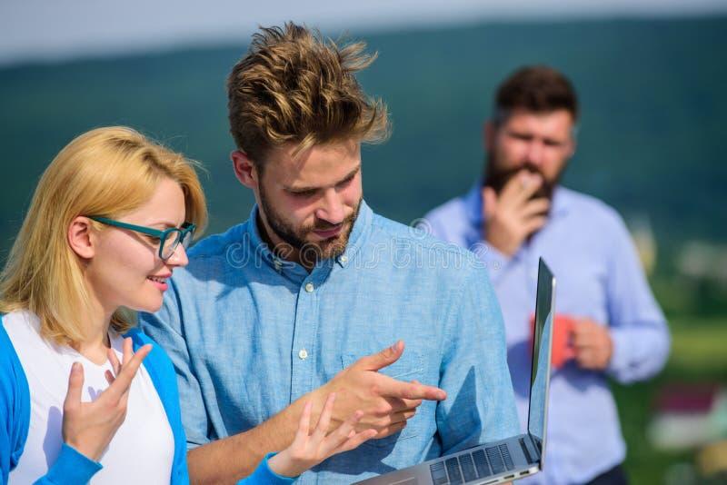 Kollegor med bärbara datorn arbetar den utomhus- soliga dagen, naturbakgrund Paret arbetar illvilja av kaffeavbrottet kollegor royaltyfria foton