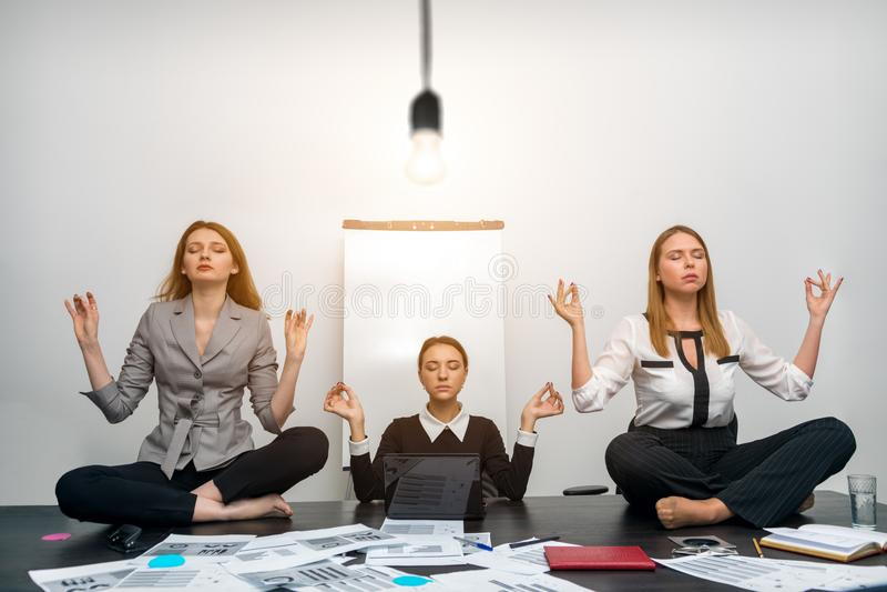 Kollegor mediterar i regeringsställning under en ljus kula arkivbilder