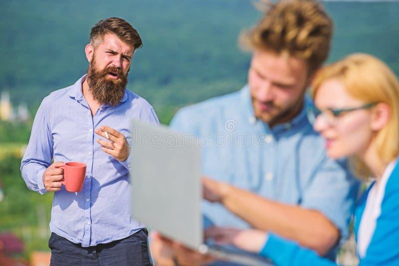 Kollegor som arbetar bärbara datorn, framstickande som röker medan kaffeavbrott på bakgrund Arbetsnarkomanbegrepp Paret arbetar t royaltyfri fotografi