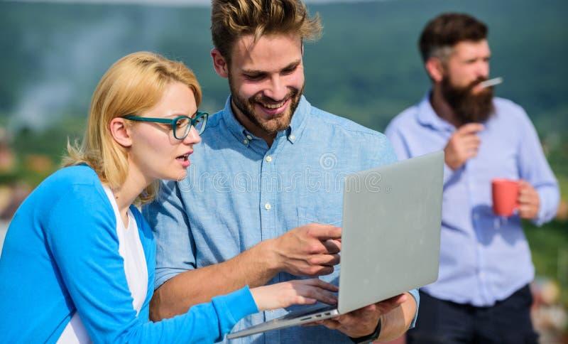Kollegor som arbetar bärbara datorn, framstickande som röker medan kaffeavbrott på bakgrund Kollegor med bärbara datorn arbetar u royaltyfria foton