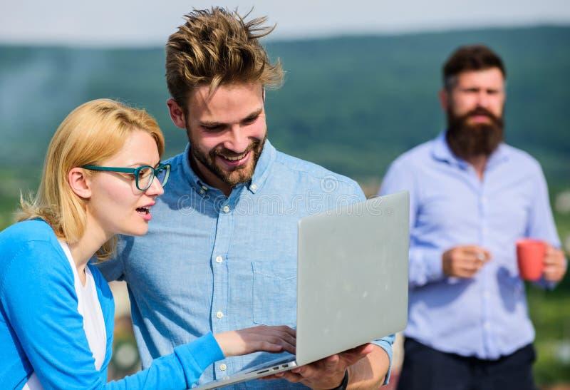 Kollegor som arbetar bärbara datorn, framstickande som röker medan kaffeavbrott på bakgrund Paret arbetar illvilja av kaffeavbrot royaltyfri foto