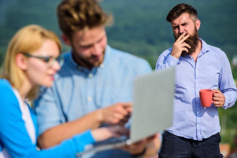 Kollegor som arbetar bärbara datorn, framstickande som röker medan kaffeavbrott på bakgrund Paret arbetar illvilja av kaffeavbrot royaltyfri bild