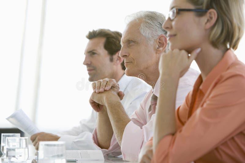 Kollegor som betalar uppmärksamhet i konferensrum arkivfoto