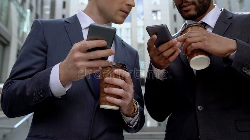 Kollegor som diskuterar nyheterna på kaffeavbrottet som surfar internet på smartphones arkivbild