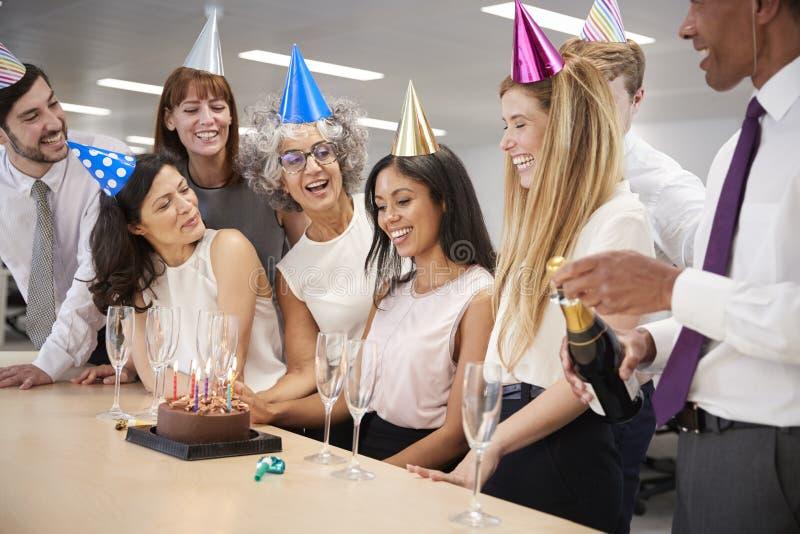 Kollegor som firar en födelsedag i kontoret med en kaka arkivbild