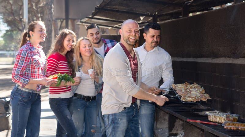 Kollegor som gör gallret på picknicken royaltyfri bild