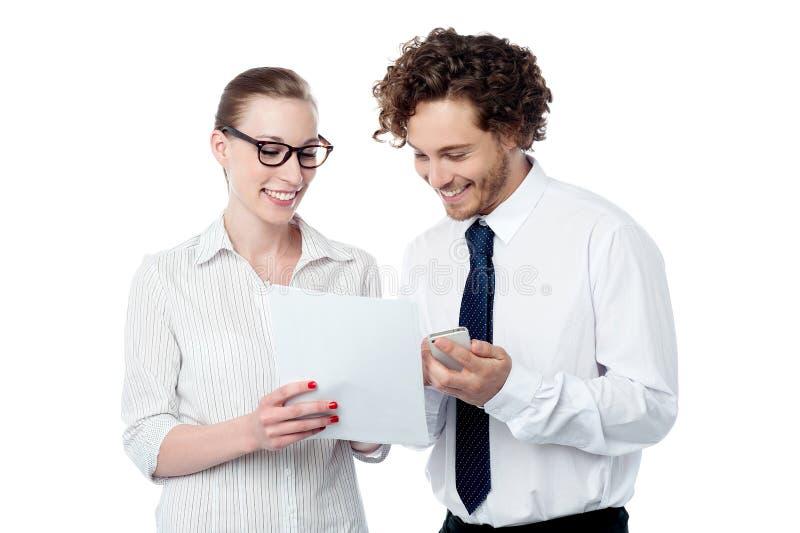 Kollegor som granskar affärsdokumentet arkivbild