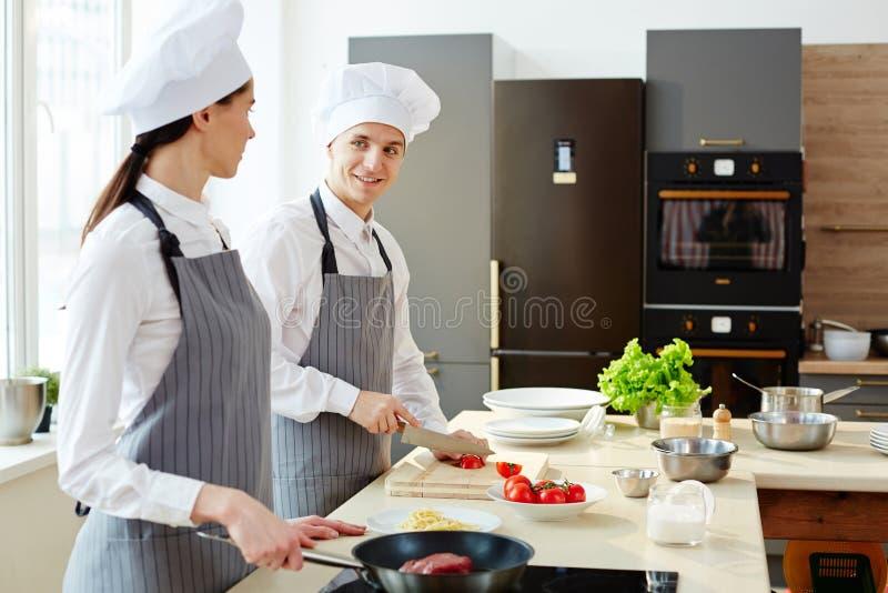 Kollegor som lagar mat och pratar i kök arkivfoto