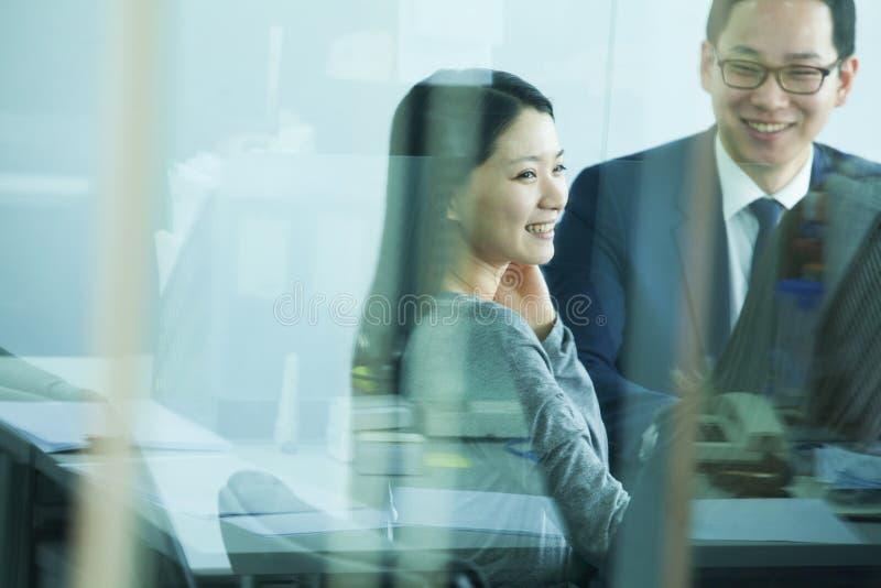 Kollegor som möter i konferensrum, skott till och med exponeringsglas arkivbilder