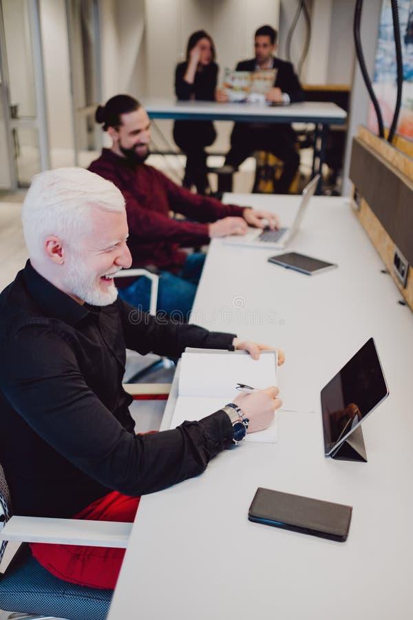 Kollegor som skrattar i kontoret, medan arbeta arkivfoton