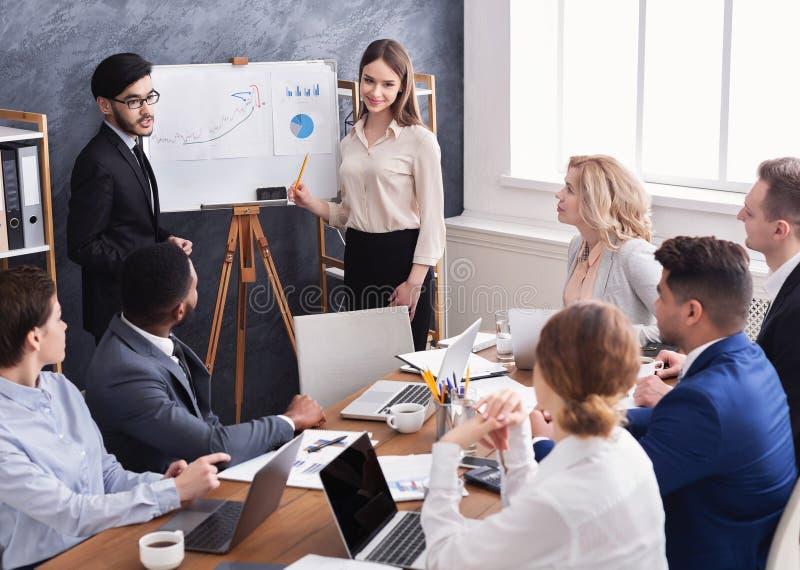 Kollegor som visar diagram på flipboard på kontoret arkivfoton