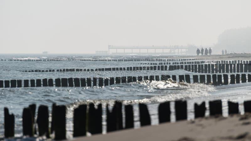 Kolobrzeg, Polonia 28 Juli 2018 Mattina nebbiosa sulla gente visibile della spiaggia polacca, sul mare, sugli schermi e sui frang immagini stock