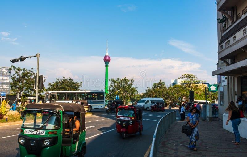 Kolombo Sri Lanka, Kwiecień, - 5, 2019: W centrum Kolombo uliczna scena z Lotus wierza w tuk-tuk na ulicie i tle obrazy royalty free