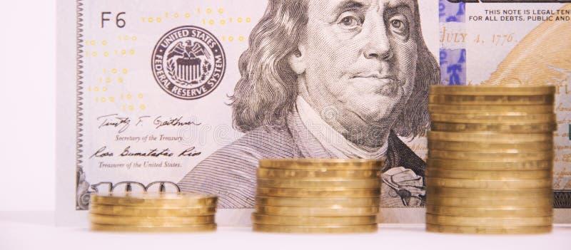 Kolommen van gouden muntstukken van verschillende hoogten tegen de achtergrond van honderd dollarsbenaming stock afbeelding